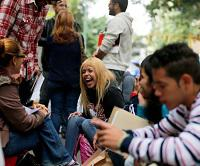 Daniela Rodríguez ríe con sus amigos mientras espera fuera del Consulado de Irlanda en Caracas. Foto AP.
